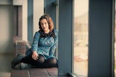 Retrato de una mujer soñadora joven que se sienta en el travesaño de la ventana Fotos de archivo