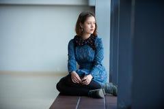 Retrato de una mujer soñadora joven que se sienta en el travesaño de la ventana Imagen de archivo libre de regalías