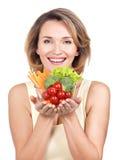 Retrato de una mujer sonriente joven con una placa de verduras. Imagen de archivo