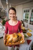 Retrato de una mujer sonriente que muestra el pavo de la carne asada Foto de archivo libre de regalías