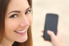 Retrato de una mujer sonriente que usa un teléfono elegante Fotografía de archivo