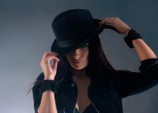 Retrato de una mujer triguena joven en un sombrero negro Imagen de archivo