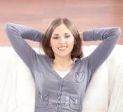 Retrato de una mujer triguena que se relaja en un sofá Imágenes de archivo libres de regalías