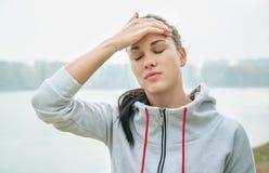 Retrato de una mujer triste joven con dolor de cabeza, cansancio o frío d Foto de archivo