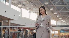 Retrato de una mujer turística del adolescente joven que visita las compras de la ciudad usando su dispositivo y sonrisa del smar Fotografía de archivo libre de regalías