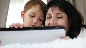 Retrato de una mujer y de un niño Una madre y un niño pequeño utilizar una tableta para llamar, para mirar una película, y tienen metrajes