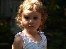 Retrato de una niña con el pelo rizado y los ojos grandes que miran seriamente en la distancia fotos de archivo libres de regalías