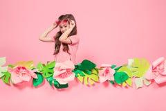 Retrato de una niña con las gafas de sol en un fondo rosado imágenes de archivo libres de regalías