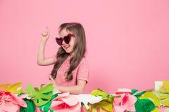 Retrato de una niña con las gafas de sol en un fondo rosado imagen de archivo