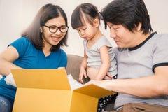Retrato de una niña con sus padres que desempaquetan las cajas imagen de archivo