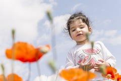 Retrato de una niña en campo de flores de la amapola delante del cielo nublado imágenes de archivo libres de regalías