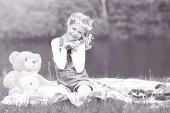 Retrato de una niña en una guirnalda con un juguete suave cerca del r imagenes de archivo