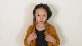 Retrato de una niña en sombrero negro, vestido negro y chaqueta marrón en un estudio almacen de metraje de vídeo