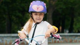Retrato de una niña en un casco púrpura de la bicicleta almacen de video