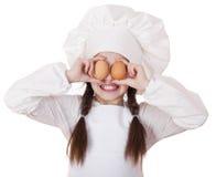 Retrato de una niña en un delantal blanco que sostiene dos el pollo e Foto de archivo