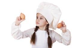 Retrato de una niña en un delantal blanco que sostiene dos el pollo e Imagen de archivo
