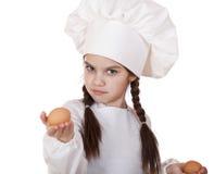 Retrato de una niña en un delantal blanco que sostiene dos el pollo e Fotografía de archivo libre de regalías