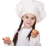 Retrato de una niña en un delantal blanco que sostiene dos el pollo e Fotografía de archivo