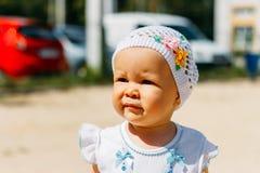 Retrato de una niña en un vestido blanco y un sombrero blanco con las flores en el fondo de coches, en el patio, un niño en foto de archivo