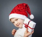 Retrato de una niña encantadora en el sombrero de Papá Noel imagenes de archivo