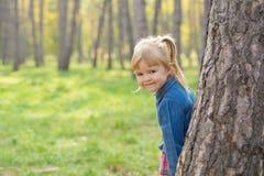 Retrato de una niña feliz con una sonrisa en su cara que oculta detrás de un árbol foto de archivo