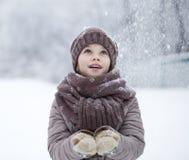 Retrato de una niña feliz en el fondo de un PA del invierno Foto de archivo libre de regalías