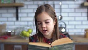 Retrato de una niña hermosa en una camisa de tela escocesa que lee un libro que se sienta en la tabla de cocina almacen de video
