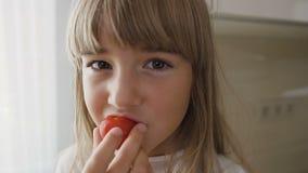 Retrato de una niña hermosa en el vestido blanco que come los tomates maduros sabrosos en la cocina Primer Cabrito lindo almacen de video