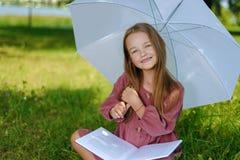 Retrato de una niña hermosa en el vestido de Borgoña el niño sonríe y lee el libro en parque imagen de archivo