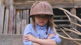 Retrato de una niña hermosa en un casco protector viejo metrajes