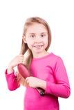 Retrato de una niña hermosa que cepilla su pelo largo. Concepto del cuidado del cabello. Foto de archivo