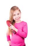 Retrato de una niña hermosa que cepilla su pelo largo. Concepto del cuidado del cabello. Fotografía de archivo