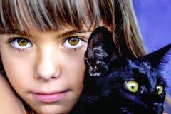 Retrato de una niña hermosa que sostiene un gato negro Fotografía de archivo libre de regalías
