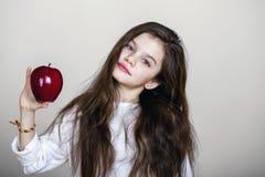 Retrato de una niña hermosa que sostiene una manzana roja Imagen de archivo libre de regalías