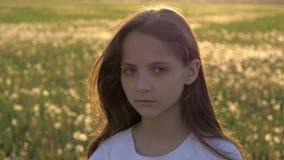 Retrato de una niña linda con el pelo largo fondo de un campo con primavera de los dientes de león metrajes