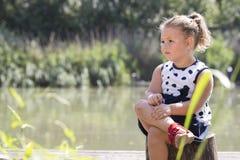 Retrato de una niña linda en un vestido mientras que se sienta al lado de Foto de archivo libre de regalías