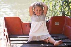 Retrato de una niña linda mientras que se sienta en un barco en un lago Imagen de archivo