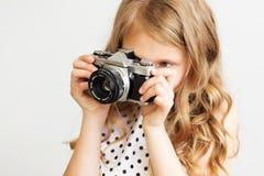 Retrato de una niña preciosa con la cámara vieja de la película de SLR Fotografía de archivo