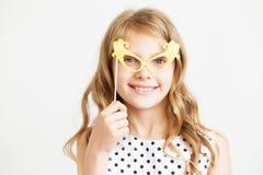 Retrato de una niña preciosa con los vidrios divertidos del papel del partido Imagen de archivo libre de regalías
