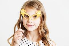 Retrato de una niña preciosa con los vidrios divertidos del papel del partido Imagen de archivo