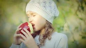 Retrato de una niña que come Apple rojo en el parque almacen de metraje de vídeo
