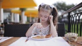 Retrato de una niña que come el almuerzo Niña en un café de la calle que aprende comer con un cuchillo y una bifurcación almacen de video