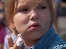 Retrato de una niña que come el caramelo de algodón imagen de archivo