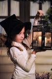 Retrato de una niña que mira la vela en la linterna Fotos de archivo libres de regalías
