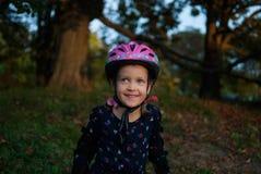 Retrato de una niña de risa - patinador del rodillo en un casco y cojines de codo imágenes de archivo libres de regalías