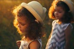 Retrato de una niña rizada triste y de su hermana gemela Daño de la niña Las niñas pequeñas en sombreros con puesta del sol calie imagen de archivo