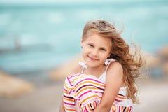 Retrato de una niña rubia hermosa en la playa en un tro Imágenes de archivo libres de regalías