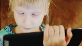 Retrato de una niña rubia que juega en una tableta digital almacen de metraje de vídeo