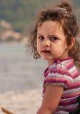 Retrato de una niña, sentándose en una playa imagen de archivo libre de regalías