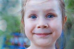 Retrato de una niña sonriente con los ojos azules en fondo blured del verano fotos de archivo